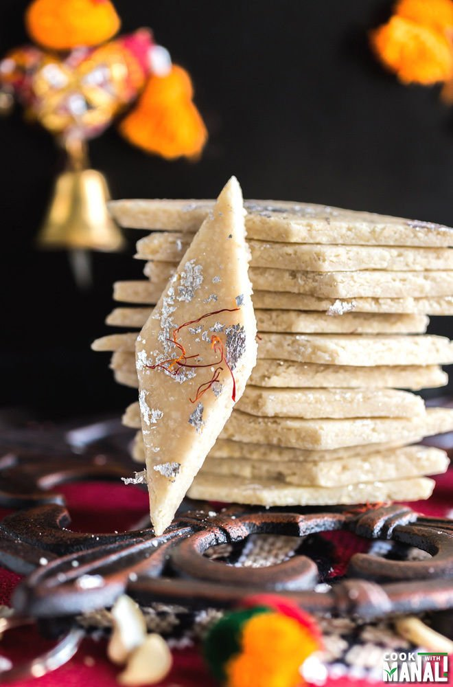 stack of kaju katli with bell hanging in the background