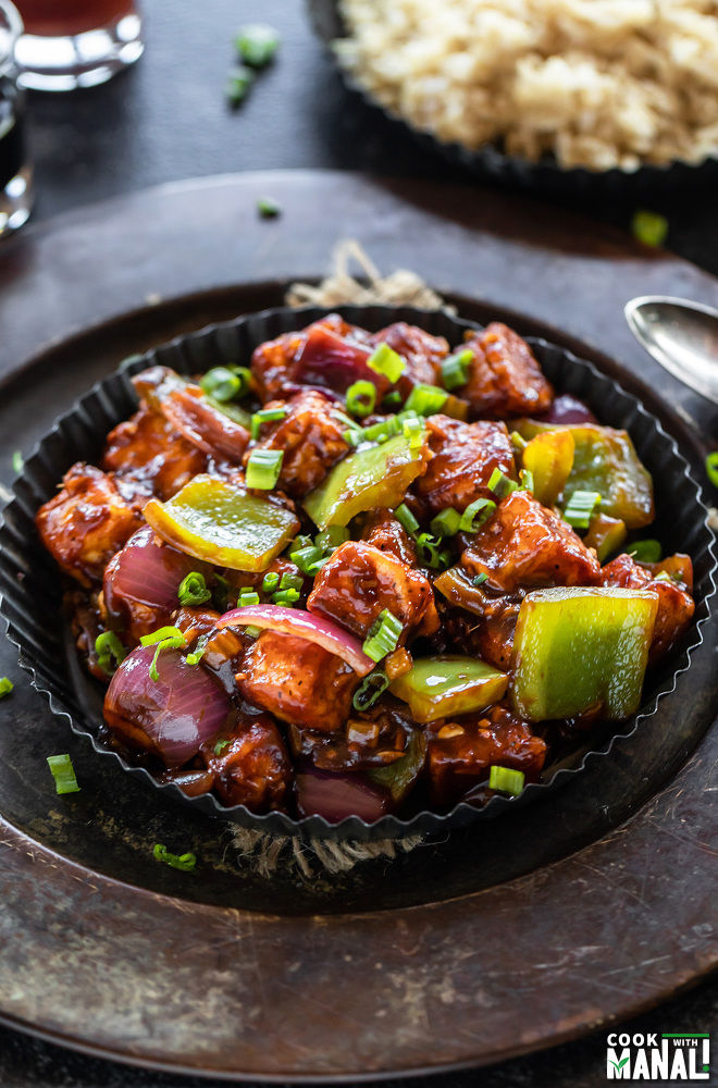 chilli paneer in a black rimmed plate