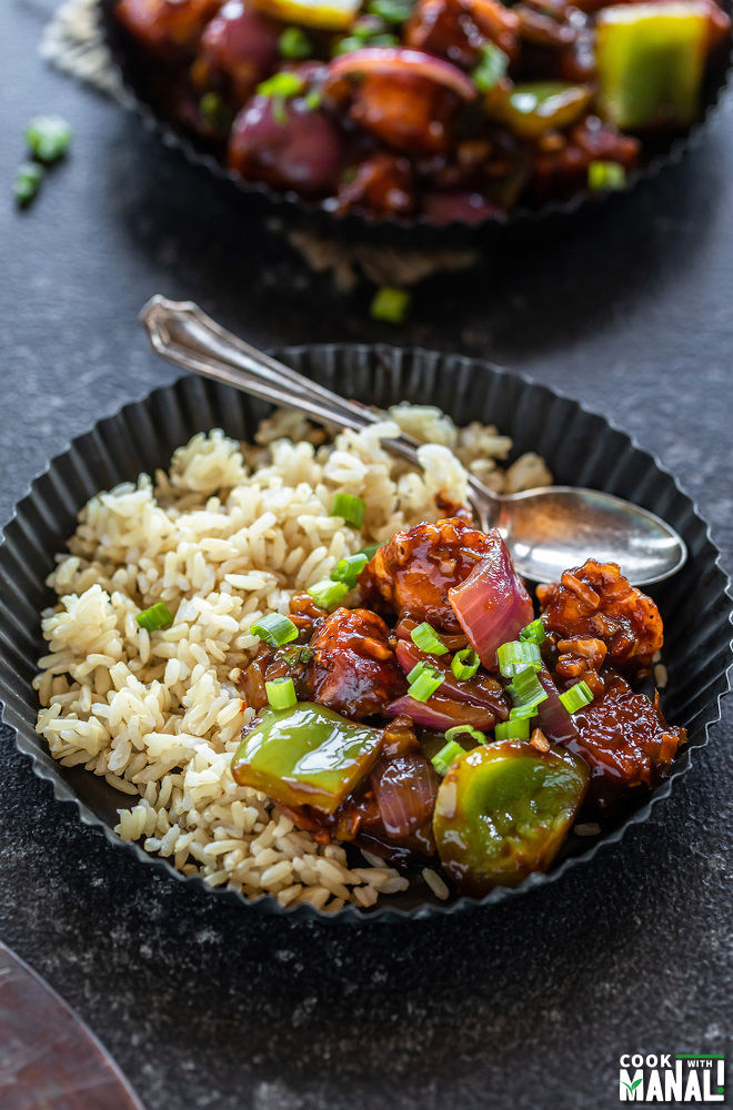 chilli paneer served with brown rice and a spoon in a black rimmed plate