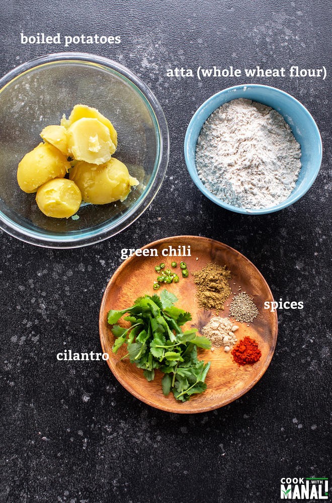 one bowl with boiled potatoes, one with flour and a plate with spices