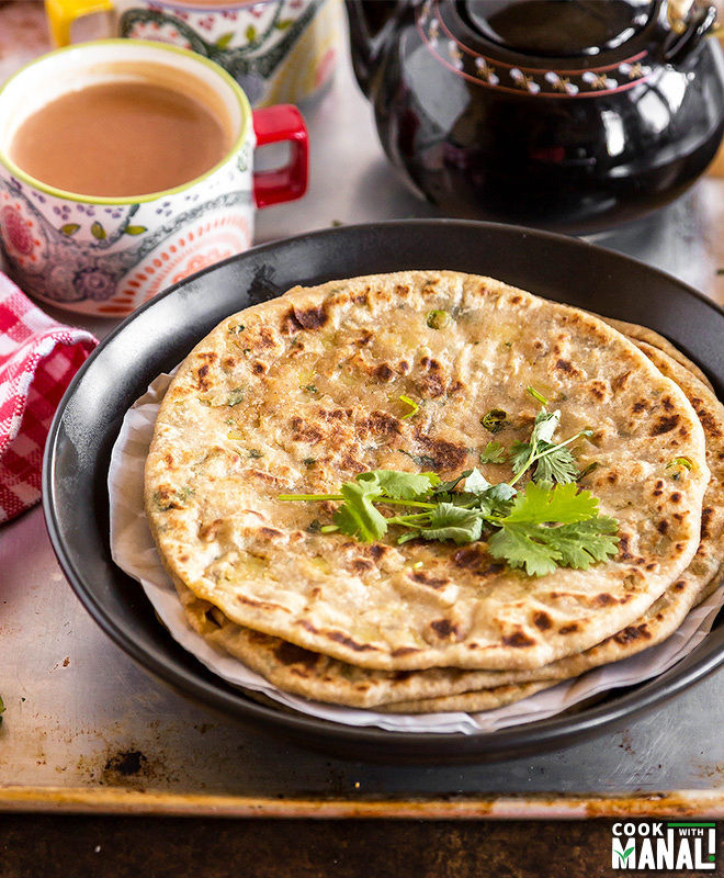 stack of parathas on a plate with cup of chai in the background