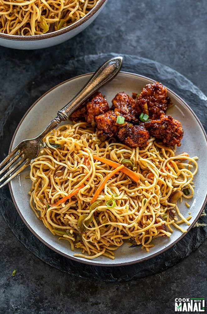 gobi manchurian served with hakka noodles in a plate along with a fork