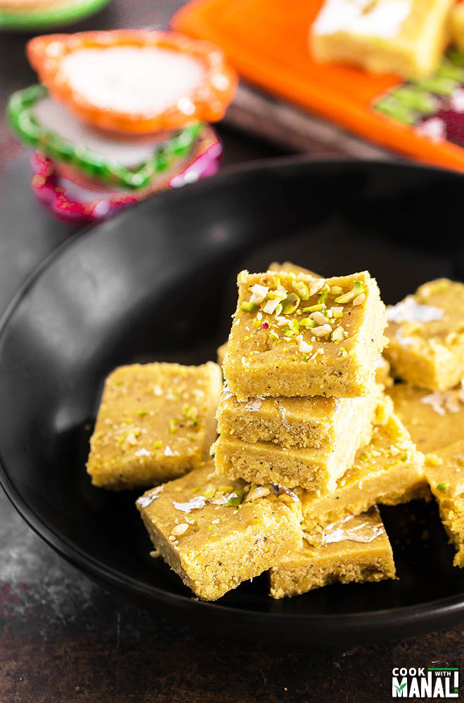 besan burfi stacked together on a black bowl with some diyas placed in the background