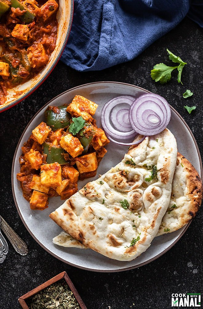kadai paneer served with naan and onion rings in a white plate