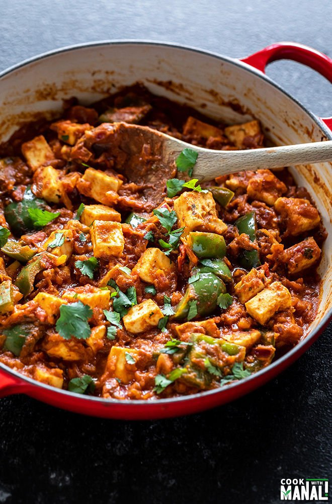 kadai paneer in a red color wok with a wooden spatula with blue napkin in the background