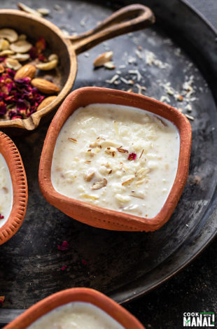 Rice Kheer served in a clay bowl and garnished with rose petals and a golden cast iron pan with nuts and rose petals in the background