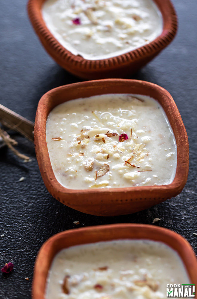 Kheer served in a clay bowl with 2 spoons on the side and more bowls of kheer on the side