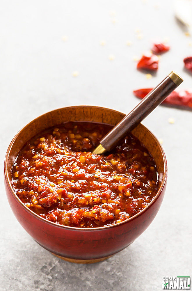 Schezwan Sauce in a red bowl with a spoon