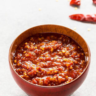 schezwan sauce in a red bowl with some broken chilies in the background
