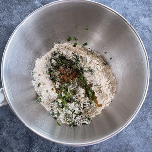a steel bowl with flour, fenugreek leaves, spices