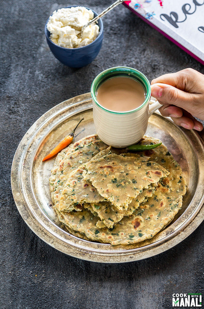 a plate with methi parathas placed on a plate with a hand holding a cup of chai placed on the same plate