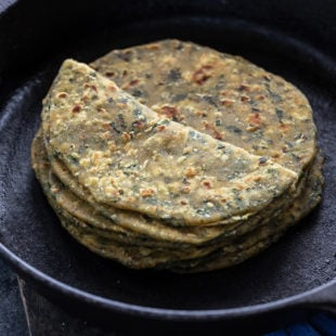 stack of methi paratha placed on a iron skillet