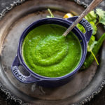cilantro chutney served in a blue bowl with a spoon and some cilantro leaves on the side