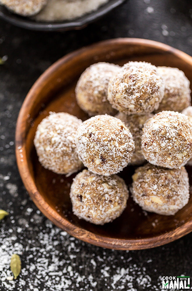 coconut cardamom energy bites in a round wooden plate