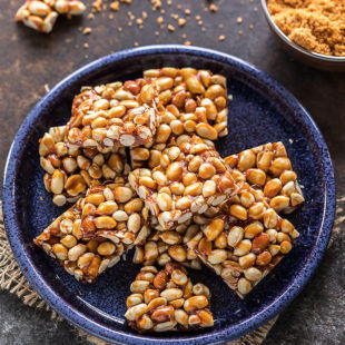 overhead shot of peanut chikki squares in a blue plate