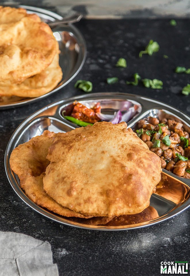 chole bhatura in a round steel plate with onions and pickle