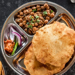 two bhaturas and chole in a steel plate with sliced onions and pickle