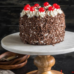 eggless black forest cake on a white marble cake stand