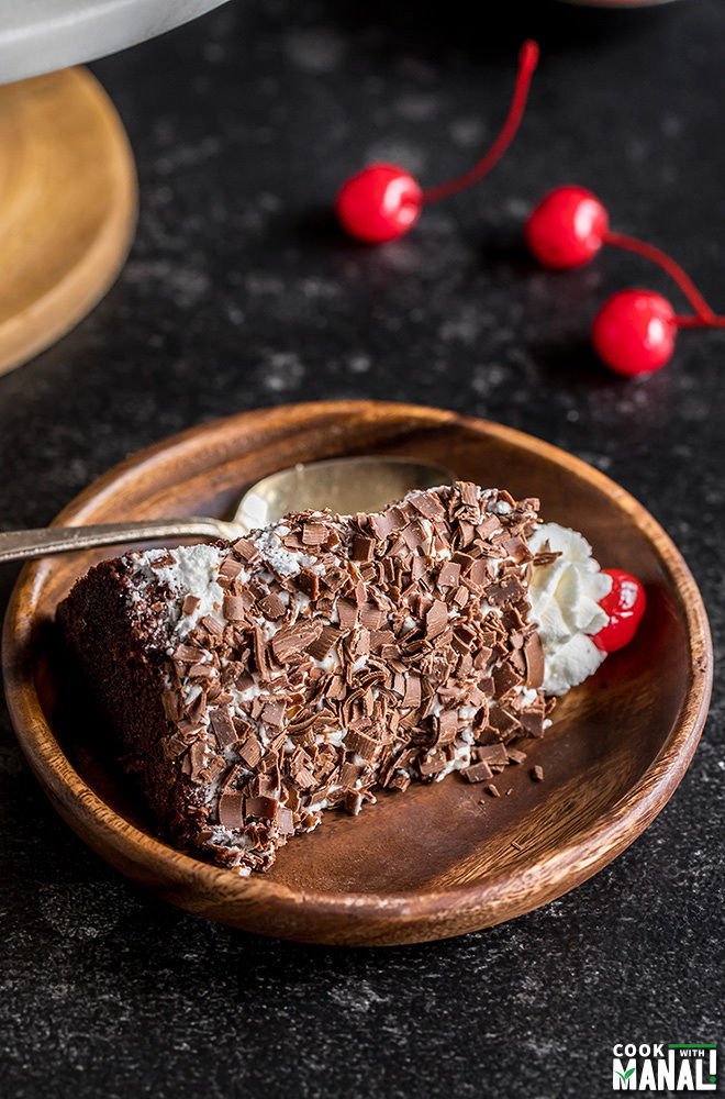 slice of eggless black forest cake in a wooden plate