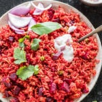 beetroot pulao in a white plate garnished with cilantro and a dollop of yogurt on top