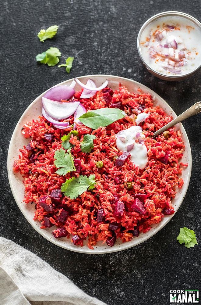 overhead shot of beetroot pulao in a white plate with a spoon and a small bowl of yogurt in the background