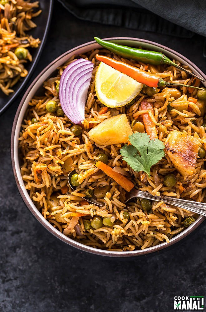 overhead shot of vegetable biryani in a black bowl