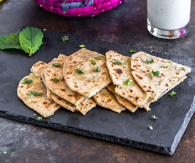 pieces of mooli paratha in a black tray with a glass of buttermilk in the background