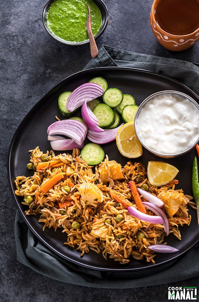 instant pot vegetable biryani in a black plate with sliced onion and lemons and bowl of yogurt