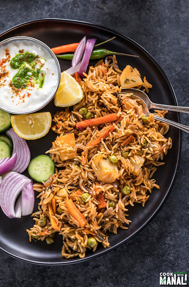 instant pot vegetable biryani in a black plate with sliced onion and lemons