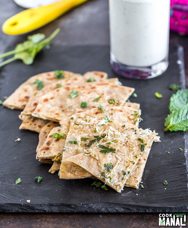 cut pieces of mooli paratha on a black tray with the front piece of paratha cut open to show the filling