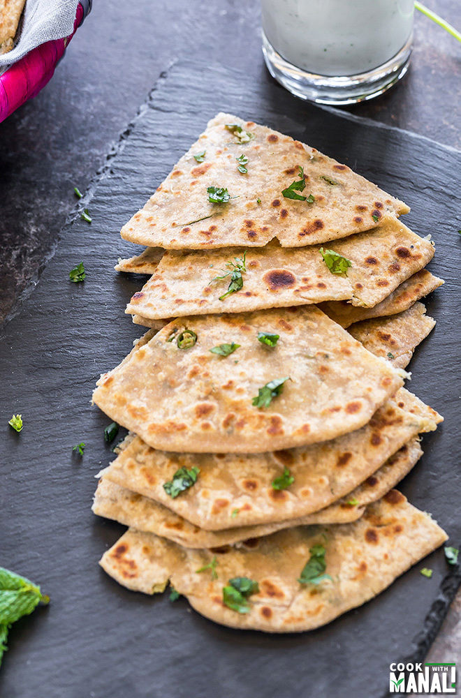 mooli paratha cut into triangular pieces and placed on a black tray