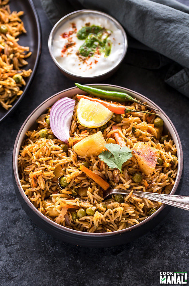overhead shot of vegetable biryani in a black bowl garnished with lemon wedge, sliced onion and green chili