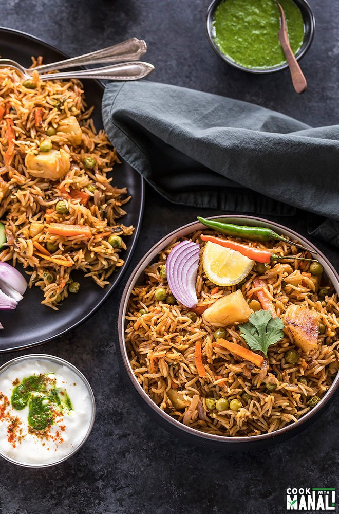 vegetable biryani in a black bowl with a bowl of yogurt on the side