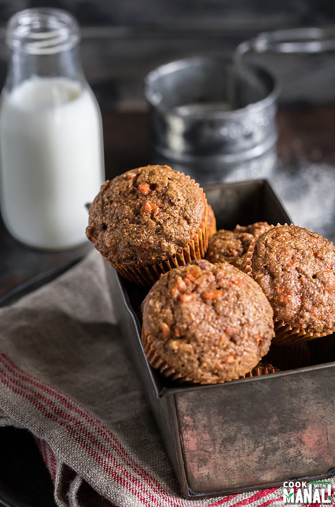 carrot muffins in a pan with a bottle of milk at the back