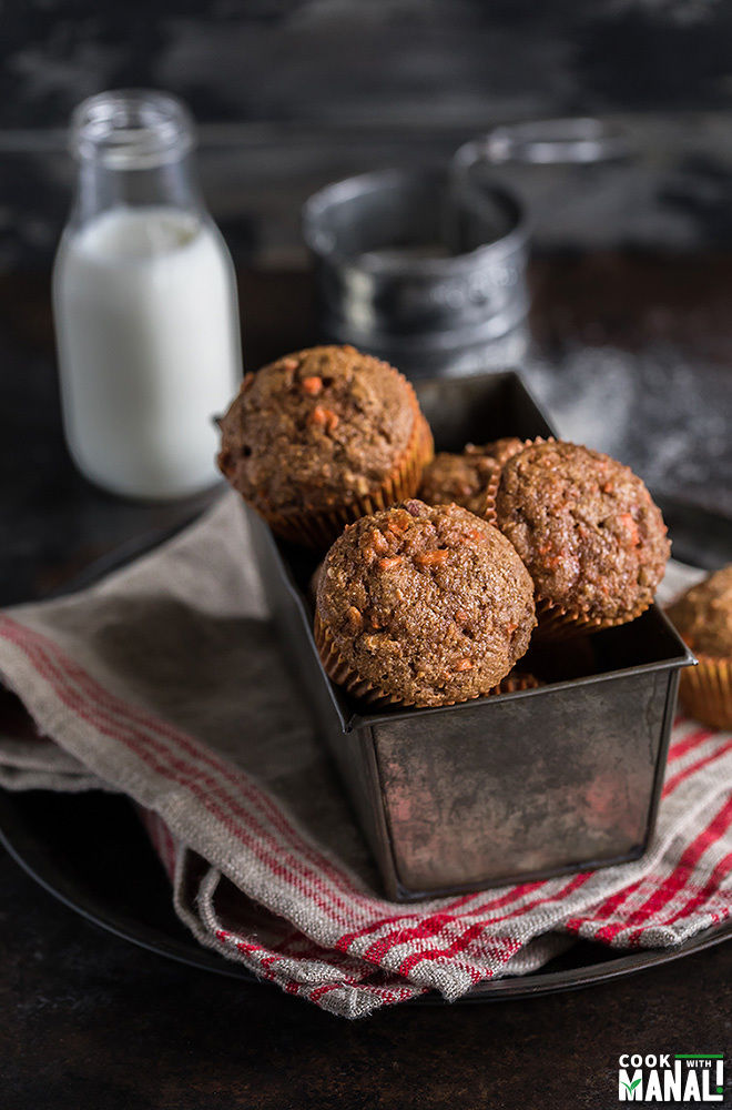 carrot muffins in a pan with a bottle of milk on the side