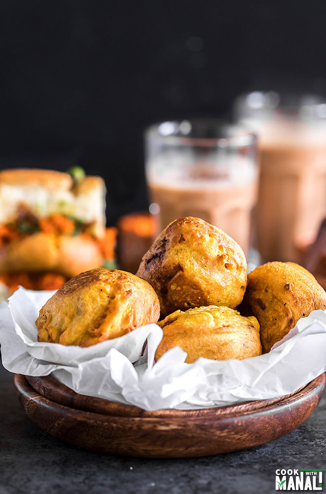 batata vada served in a wooden bowl lined with parchment paper with chutney bowls and glass of chai in the background