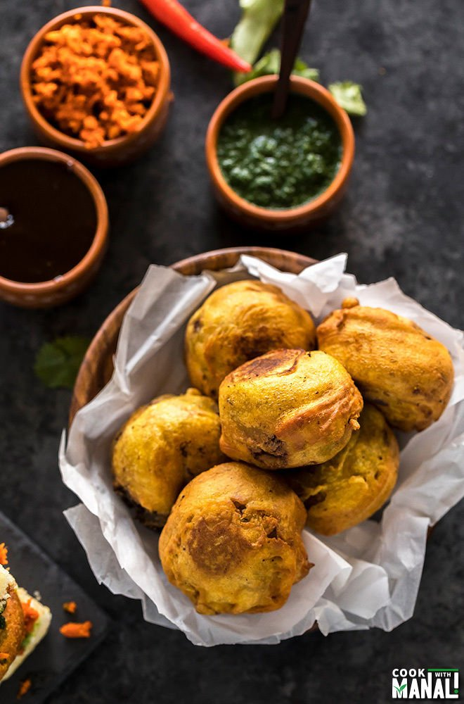 batata vada served in a wooden bowl lined with parchment paper with chutney bowls on the back