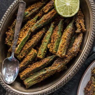 spicy bharwa bhindi in an oval brass plate, served with a side of lime