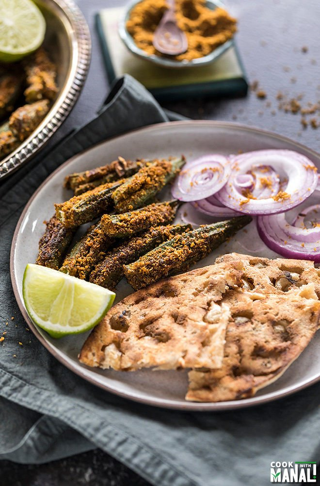 bharwa bhindi served with tandoori roti and sliced onions in a plate