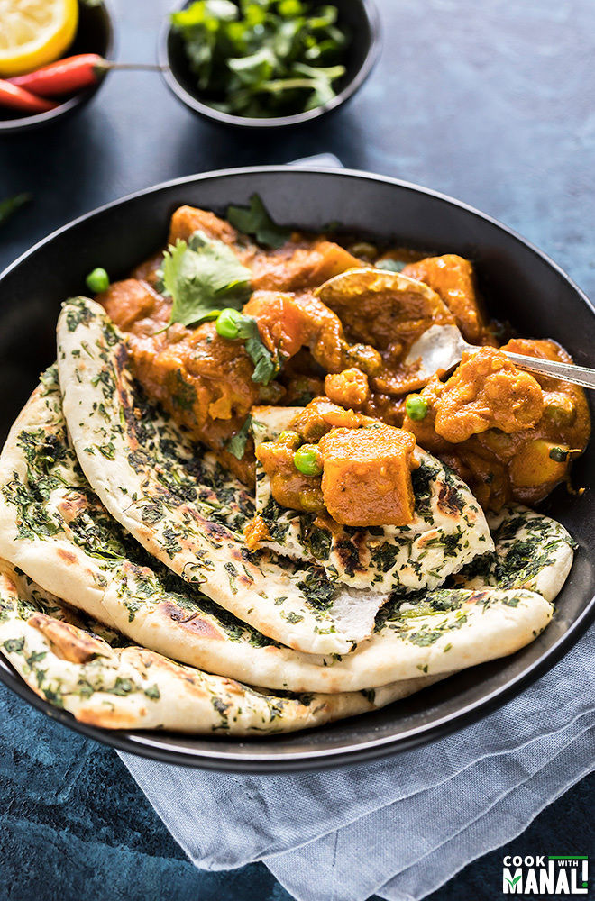 vegetable korma with naan and garnished with cilantro, served in a black bowl with a spoon