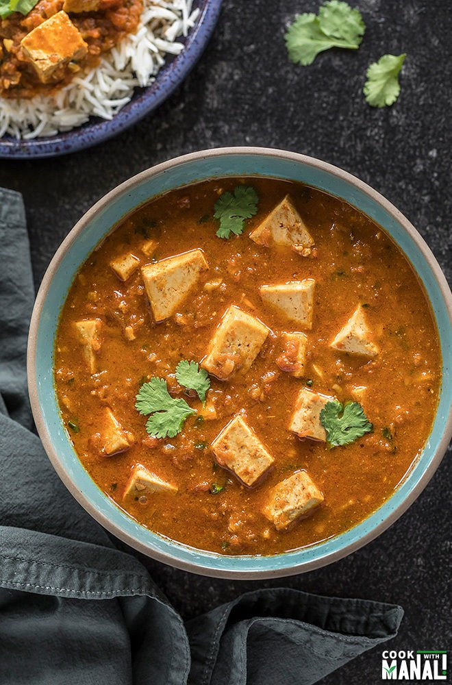 overhead shot of tofu tikka masala served in a blue bowl with a grey napkin on the side