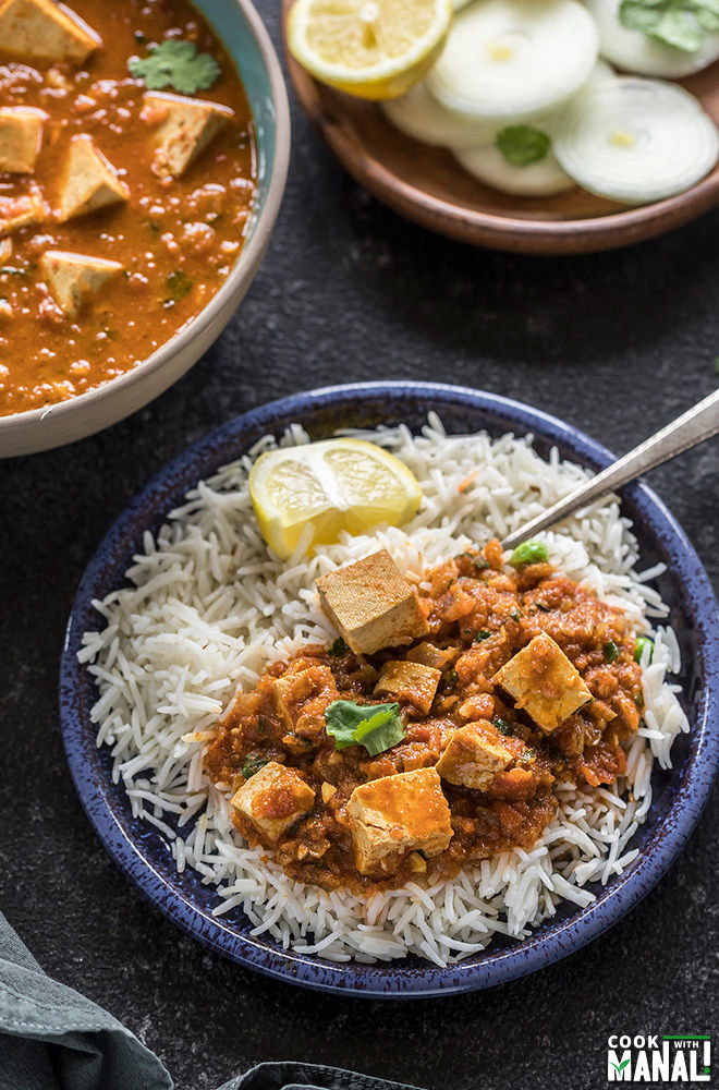 tofu tikka masala served over rice in a small blue plate
