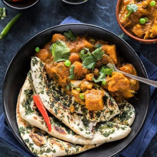 vegetable korma served along with naan in a black bowl