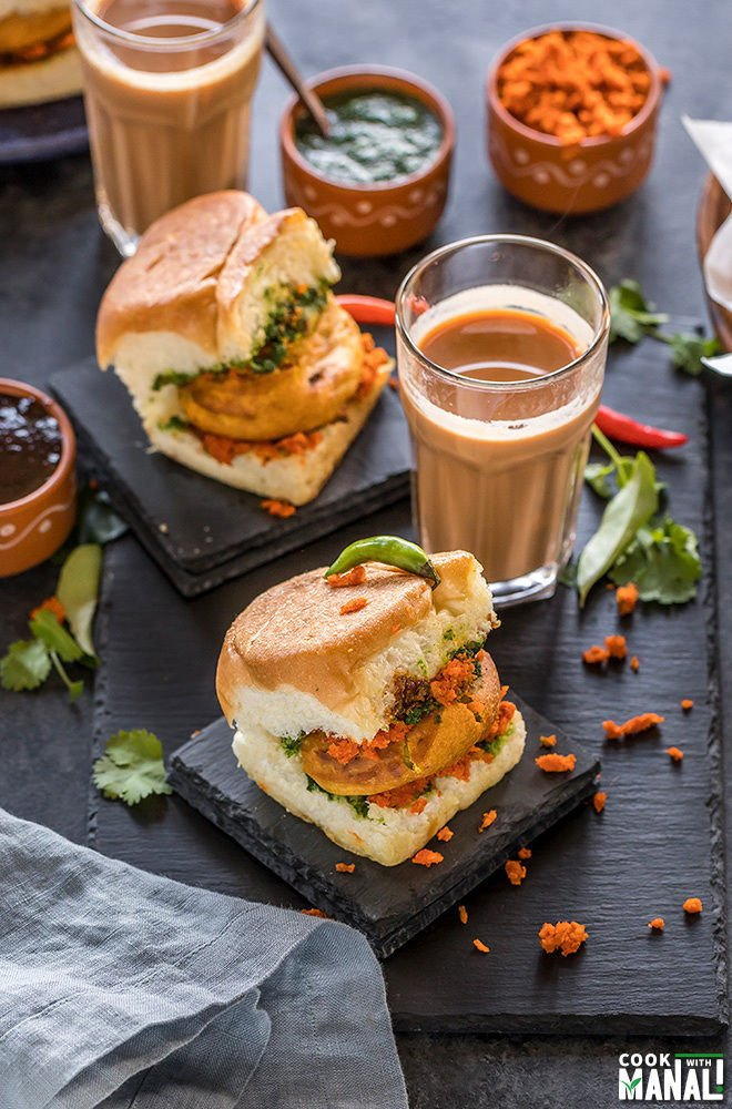 Mumbai Vada Pav placed on a black coaster with glass of chai and bowls of chutney in the background