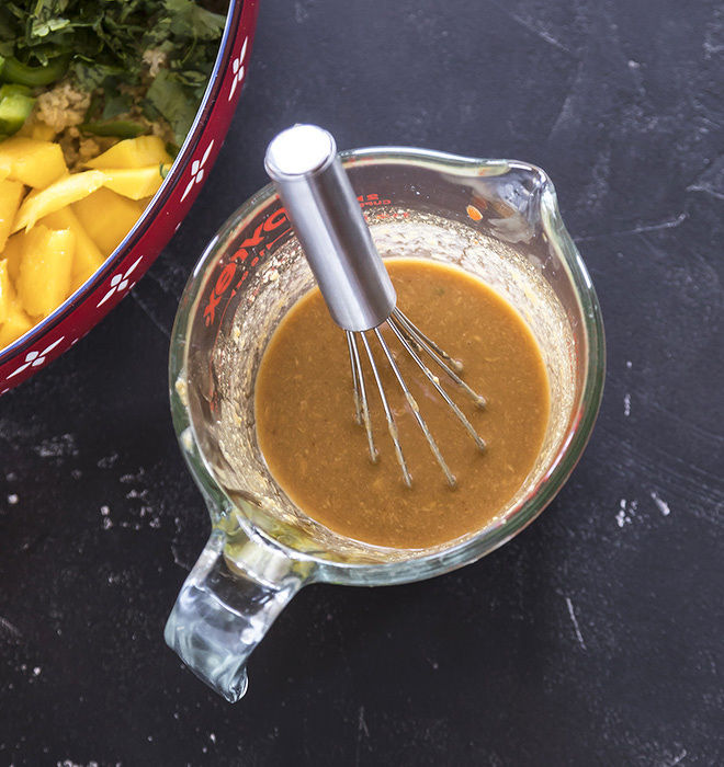 peanut ginger dressing in a measuring jar with a whisk