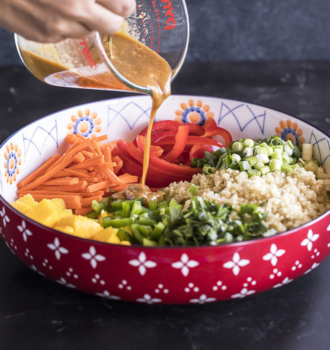 peanut ginger dressing being poured over a big bowl of quinoa salad