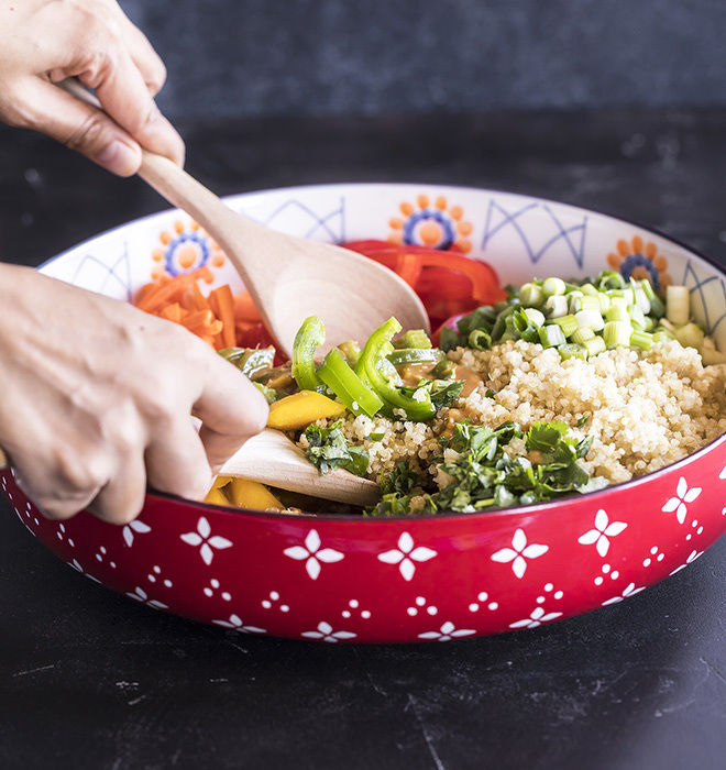 quinoa mango salad in a large bowl being tossed with two wooden spoons