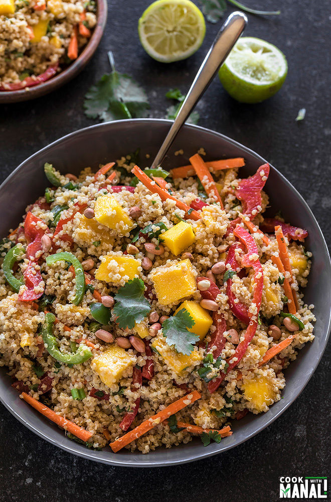 quinoa mango salad in a grey bowl with a spoon on the side