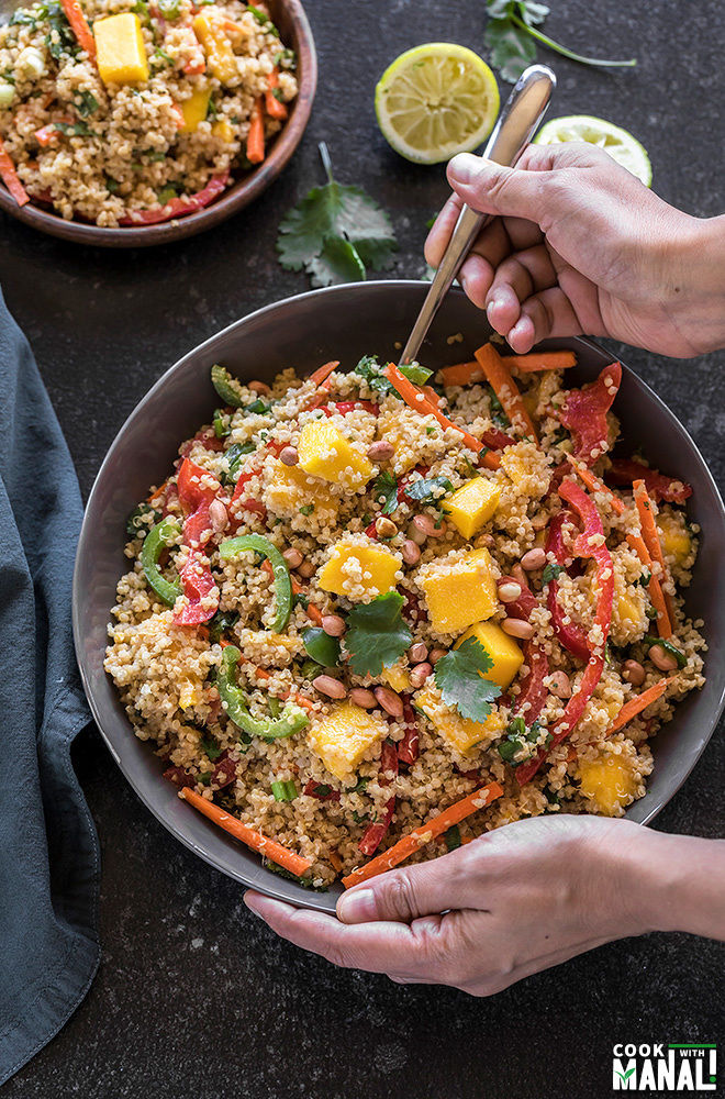 a pair of hands holding a large grey bowl of quinoa mango thai salad