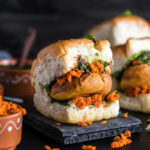 vada pav on a black coaster with chutney bowls on the back and side